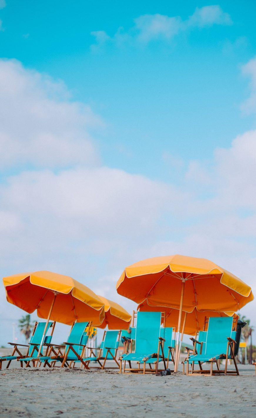 beach chairs with orange umbrellas